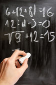 Hand writes mathematical equations on black blackboard — Stock fotografie