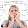Desperate woman with many mathematical equations around her - Stock Photo