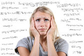 Desperate woman with many mathematical equations around her — Stockfoto