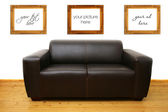 Brown leather sofa and blank photo frames on the wall — Stockfoto
