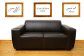 Sofá de cuero marrón y marcos de fotos en blanco en la pared — Foto de Stock