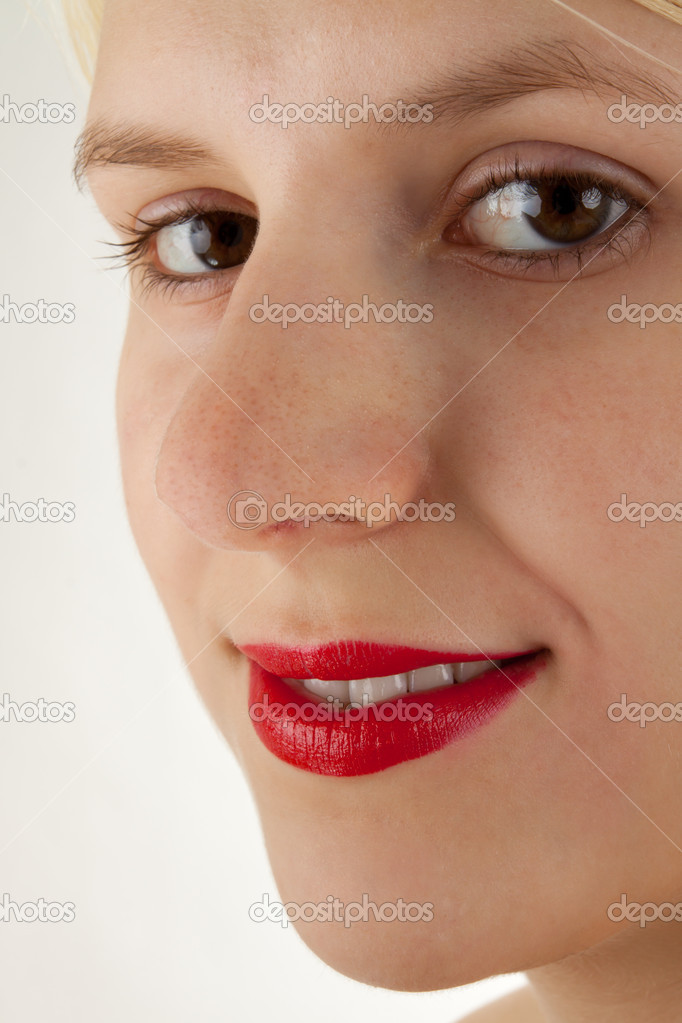 A young girl is putting lipstick on  Stock Photo #4408311