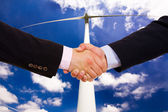 Business men hand shake over a windmill as background — Stock Photo