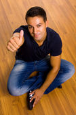 Young casual man sitting on the floor thumbs up — Stock Photo