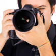 Royalty-Free Stock Photo: Close up portrait of a young photographer with camera at the stu