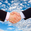 Business men hand shake over a blue sky with clouds as backgroun - Stock Photo