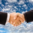 Business men hand shake over a blue sky with clouds as backgroun — Stock Photo