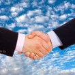 Business men hand shake over a blue sky with clouds as backgroun — Stock Photo #4116534