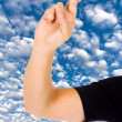 Stock Photo: Close up of a hand with fingers crossed over a blue sky with clo