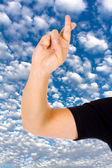 Close up of a hand with fingers crossed over a blue sky with clo — Stock Photo