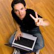 Young man sitting on the floor working on laptop computer at hom — Stock Photo