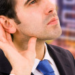 Handsome young business man listening the conversation at the of — Stock Photo #4184637