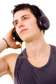 Young man listening music isolated on white — Stockfoto