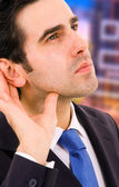 Handsome young business man listening the conversation at the of — Stock Photo