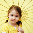 Little girl with yellow parasol — Stock Photo