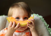 Baby eating cantaloupe — Stock Photo