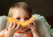 Baby eating cantaloupe — Stock Photo