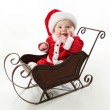 Smiling santa baby sitting in a sleigh — Stock Photo #4521170