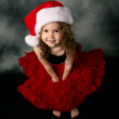 Little girl wearing Christmas santa hat and red pettiskirt — Stock Photo