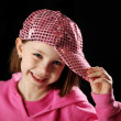 Female child wearing pink sparkly baseball cap - Stock Photo