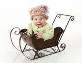 Smiling baby sitting in a sled — Stock Photo