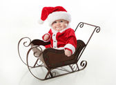 Santa baby sitting in a sleigh — Stock Photo
