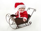 Smiling santa baby sitting in a sleigh — Stock Photo