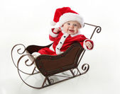Smilng santa baby sitting in a sleigh — Stock Photo