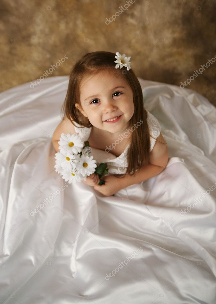Little girl trying on mommy s wedding dress stock image