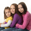 Three sisters sitting down hugging each other — Stock Photo