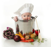 Licking baby sitting in a chef's pot — Stock Photo