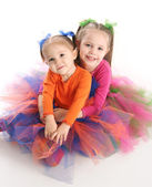 Sisters in bright tutu skirts — Stock Photo