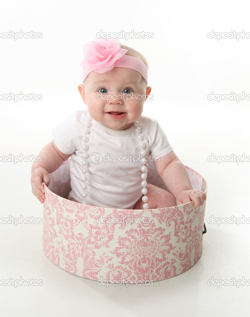 Portrait of an adorable baby girl sitting in a pink and white hatbox wearing a white shirt, pearl necklace, and pink headband with rose — Stock Photo #4620117