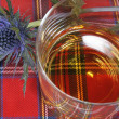 Stock Photo: Whiskey and Thistle on Tartan
