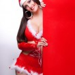 Sexy young woman in Mrs Santa Claus holding a red blank sign — Stock Photo