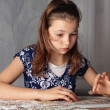 Stock Photo: Teenage girl doing puzzle