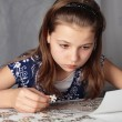 Stock Photo: Teenage girl concentrates on puzzle