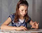 Teenage girl doing puzzle — Stock Photo