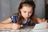 Teenage girl concentrates on puzzle — Stock Photo