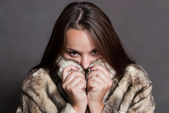 Girl hiding in fur coat — Stock Photo