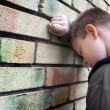 Stock Photo: Upset boy against wall