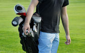 Male golfer carrying clubs, close-up — Stock Photo