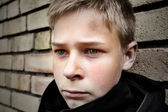 Upset boy leaning against a wall — Stok fotoğraf