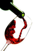Red wine pouring into wine glass — Stock Photo