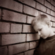 Boy leaning against a wall - Stockfoto
