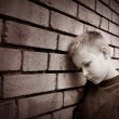 Stock Photo: Boy leaning against wall