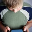 Boys hand playing portable video game — Stock Photo