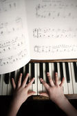 Child's hands playing on a old piano — Stock Photo