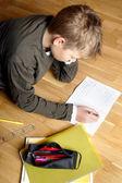 Junge schreiben auf Papier, auf dem Boden liegend — Stockfoto