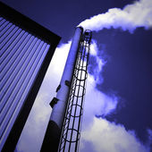 Chimney with fumes on blue clear sky — Stock Photo